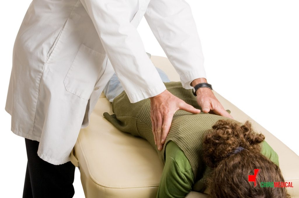 Chiropractor doing adjustment on female patient.  White background.